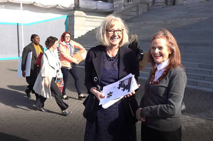 CEO Sue Chetwin (right) presenting our petition to Minister of Commerce and Consumer Affairs Jacqui Dean.