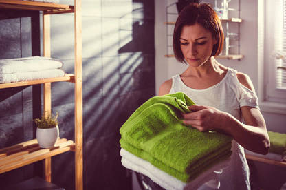 woman inspecting clean towels.