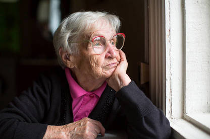 Lady in retirement home staring out of the window.
