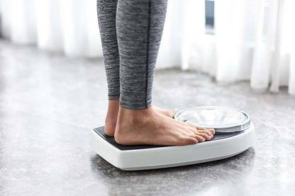 Woman weighing herself on bathroom scale.
