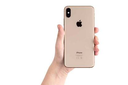 Hand holding up pink iPhone XS Max.