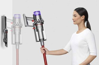 Woman mounting Dyson V11 Outsize on wall for charging.