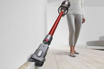 Dyson Outsize V11 cleaning against wall.