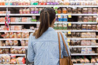 Woman looking at unit pricing at supermarket.