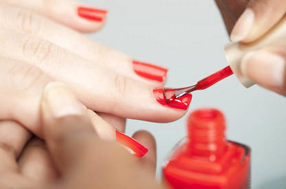 Person getting their nails painted red in a salon.