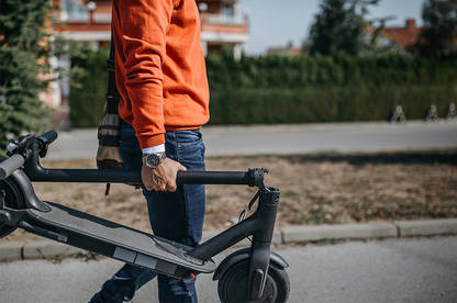 Man walking with folded electric scooter.