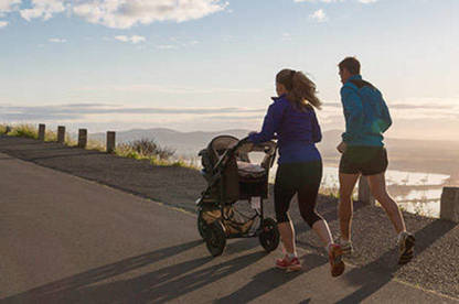 Couple running with a stroller by the ocean.