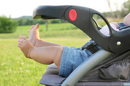 Photograph of baby's legs in a stroller.