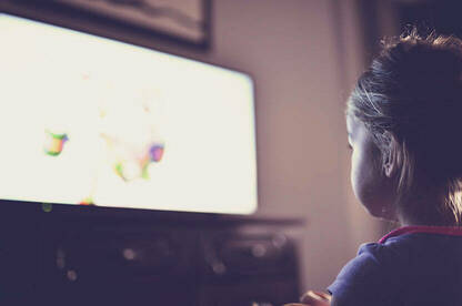 Girl sitting in front of television.