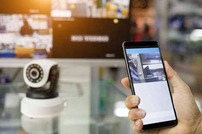 Security camera monitor in building and hand holding a smart phone.