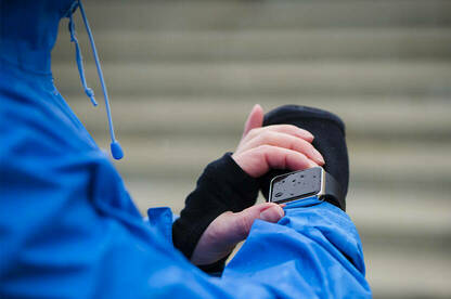 Photograph of a person using a smartwatch in the rain.