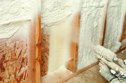 Worker spraying expandable foam insulation between wall studs