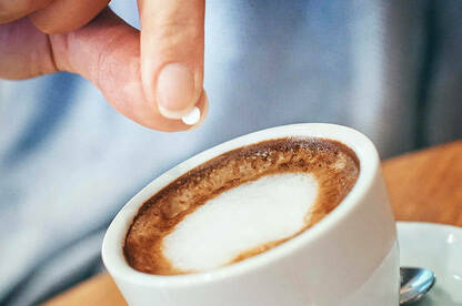 Person putting artificial sweetener tablet in coffee.