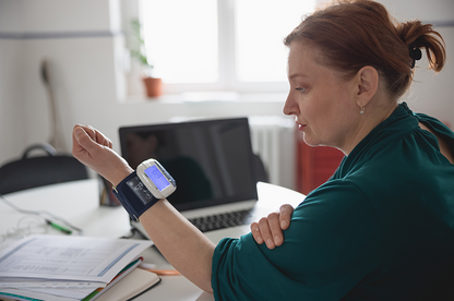 Woman checking blood pressure with home wrist blood pressure monitor.