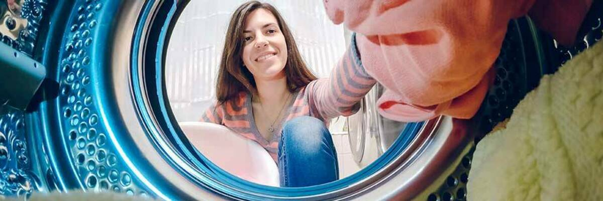 Smiling woman putting clothes in washing machine.
