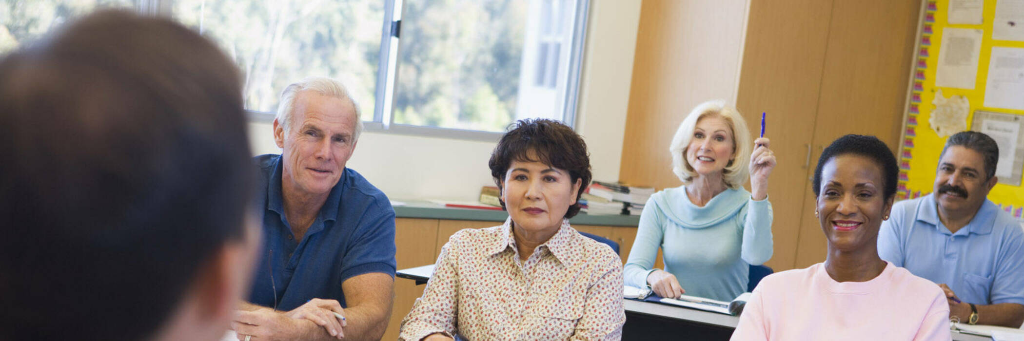 Adult female student raising hand in class