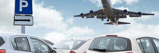 plane taking off over airport car park