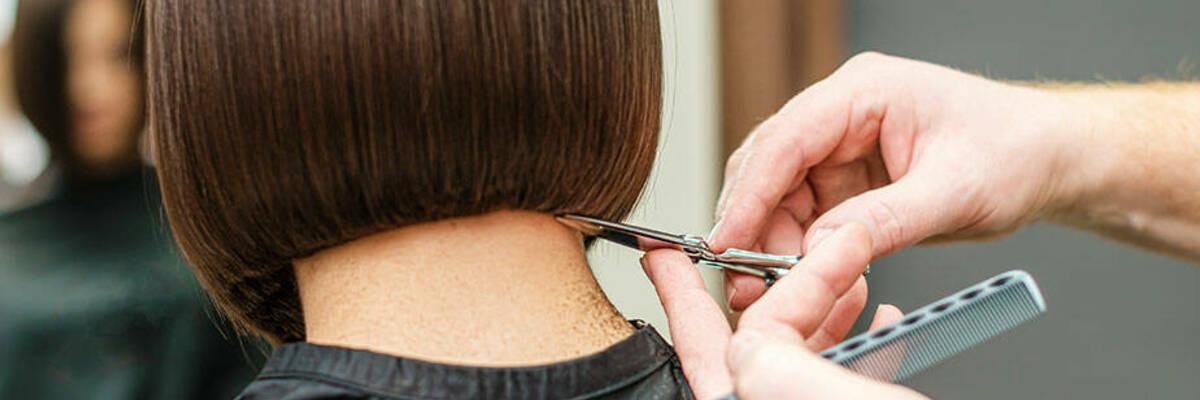 Woman getting hair cut in salon.