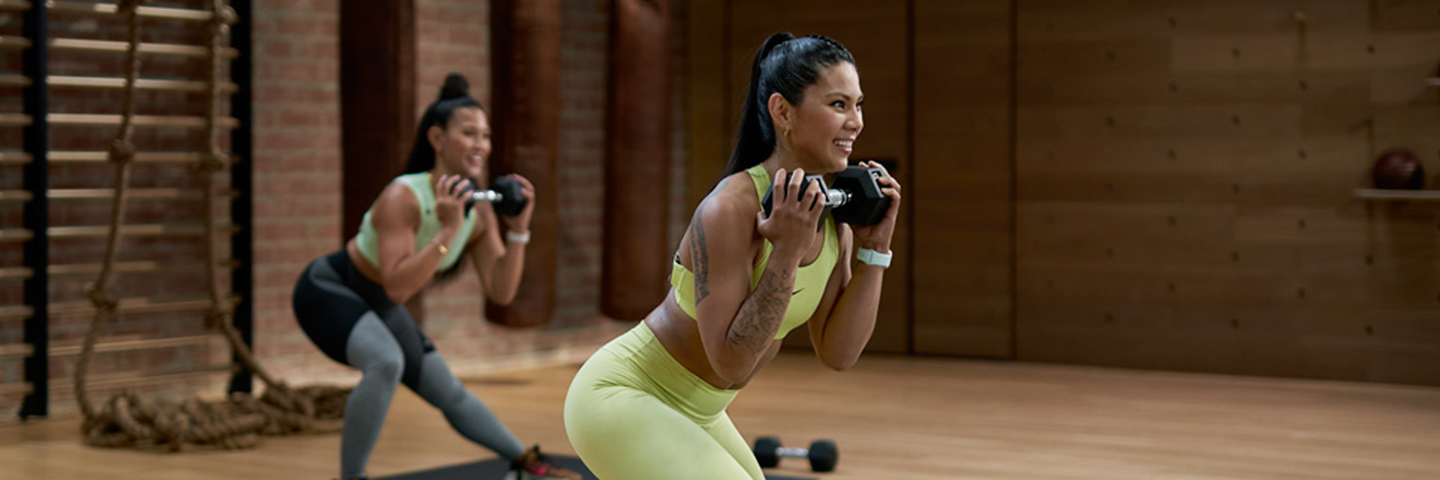 Photograph of Apple Fitness+ trainers exercising with weights.