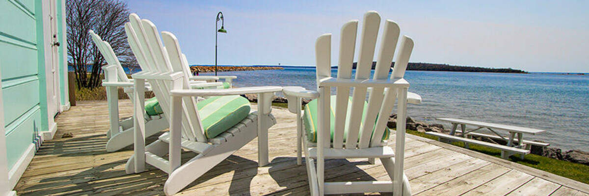Chairs on wooden deck looking over water.