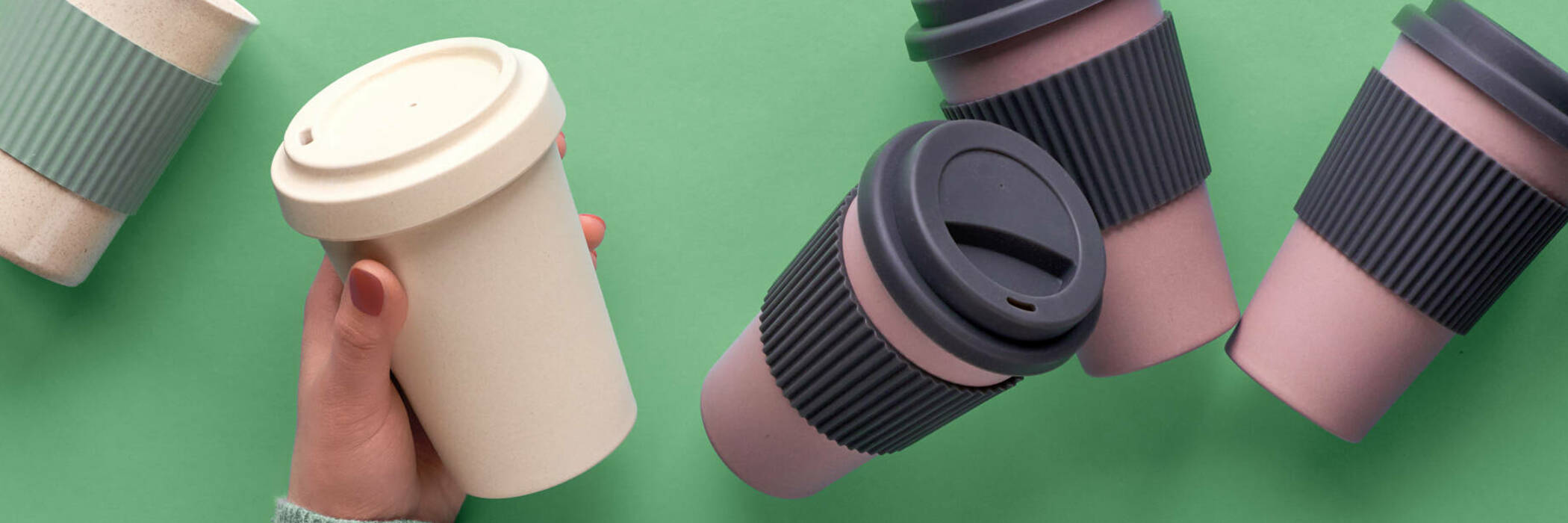 Reusable coffee cups on green background