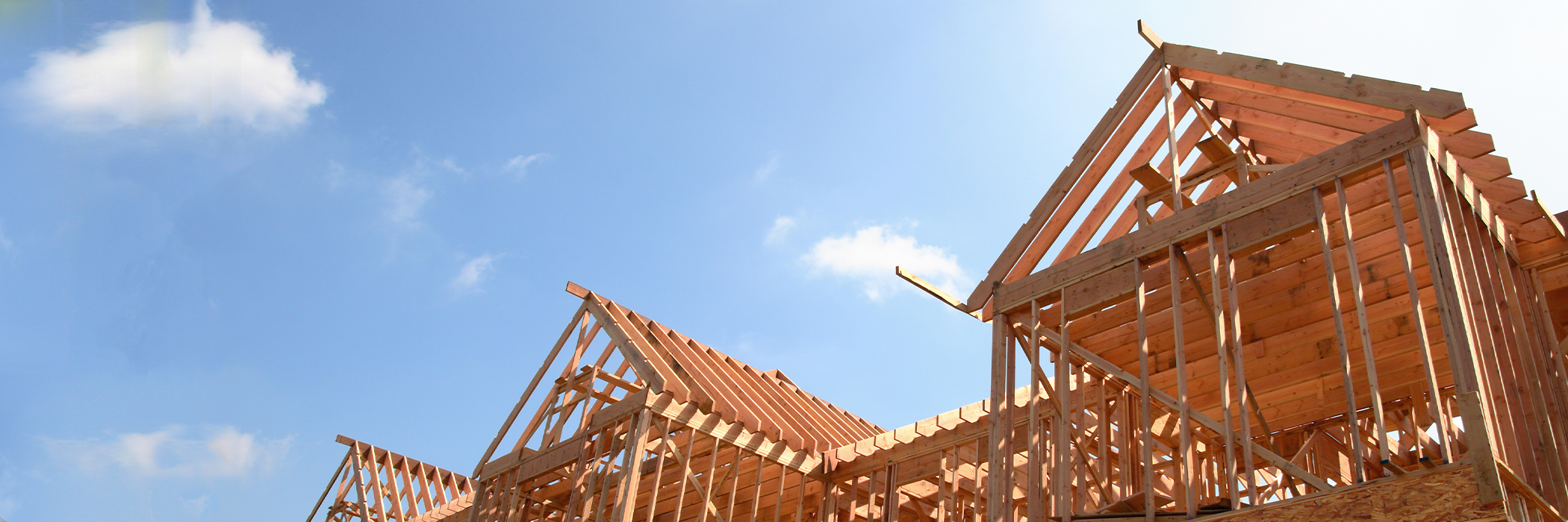 Wooden frame of a new house under construction against a bright sunny sky.