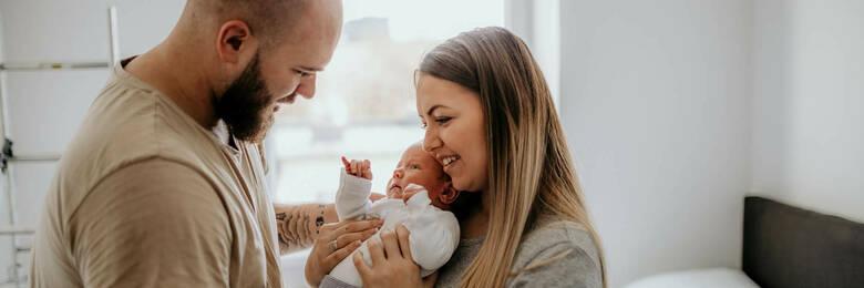 Happy parents holding newborn baby.