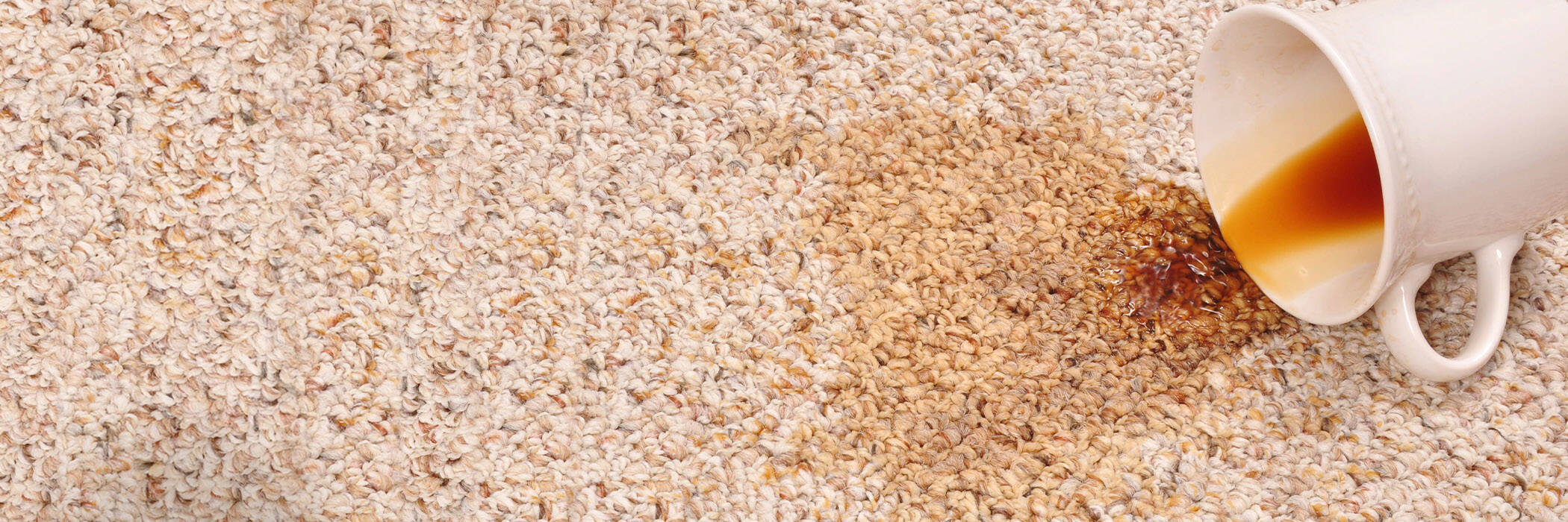 Close-up of coffee spilling on carpet.