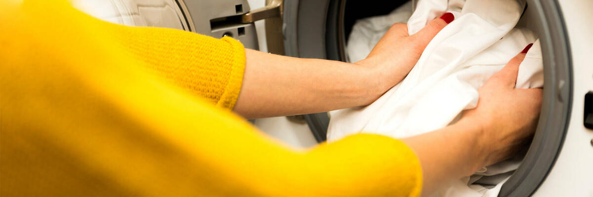 Woman loading clothes in clothes dryer.
