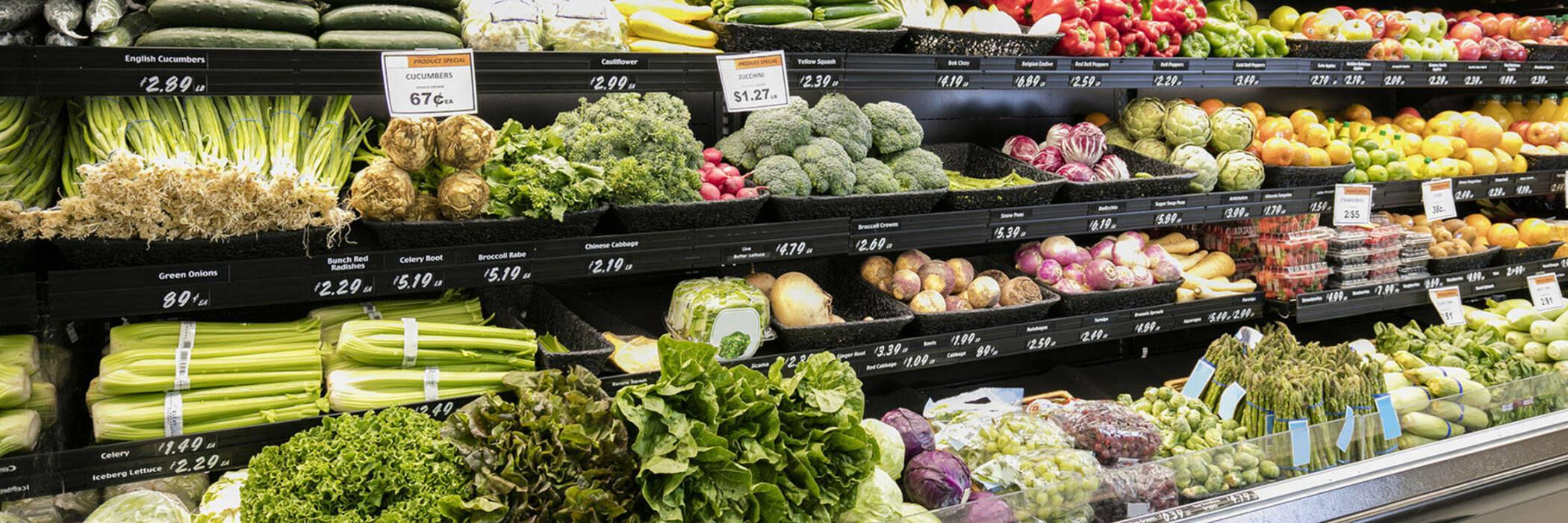 Supermarket shelves full of fruit and vegetables.