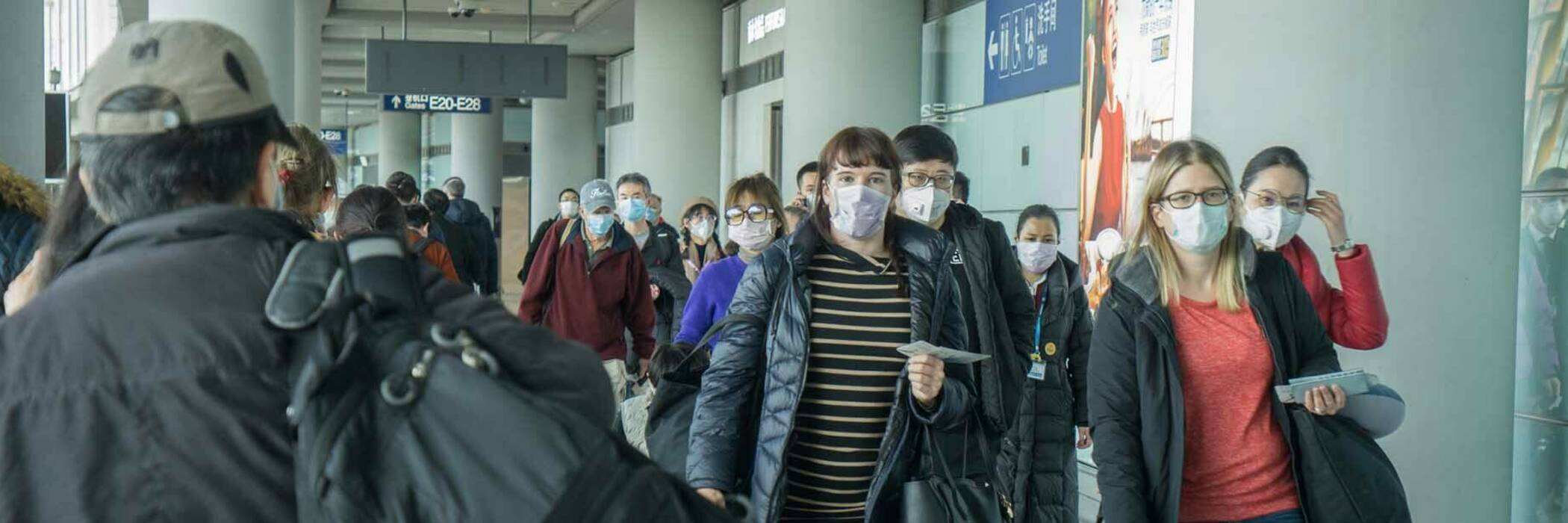Travellers in airport wearing face masks.