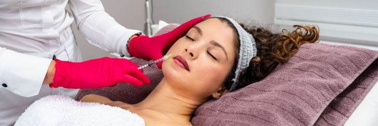 Woman lying on bed being administered botox filler.