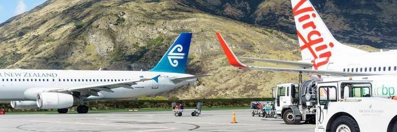 Air New Zealand and Virgin airplanes on tarmac.