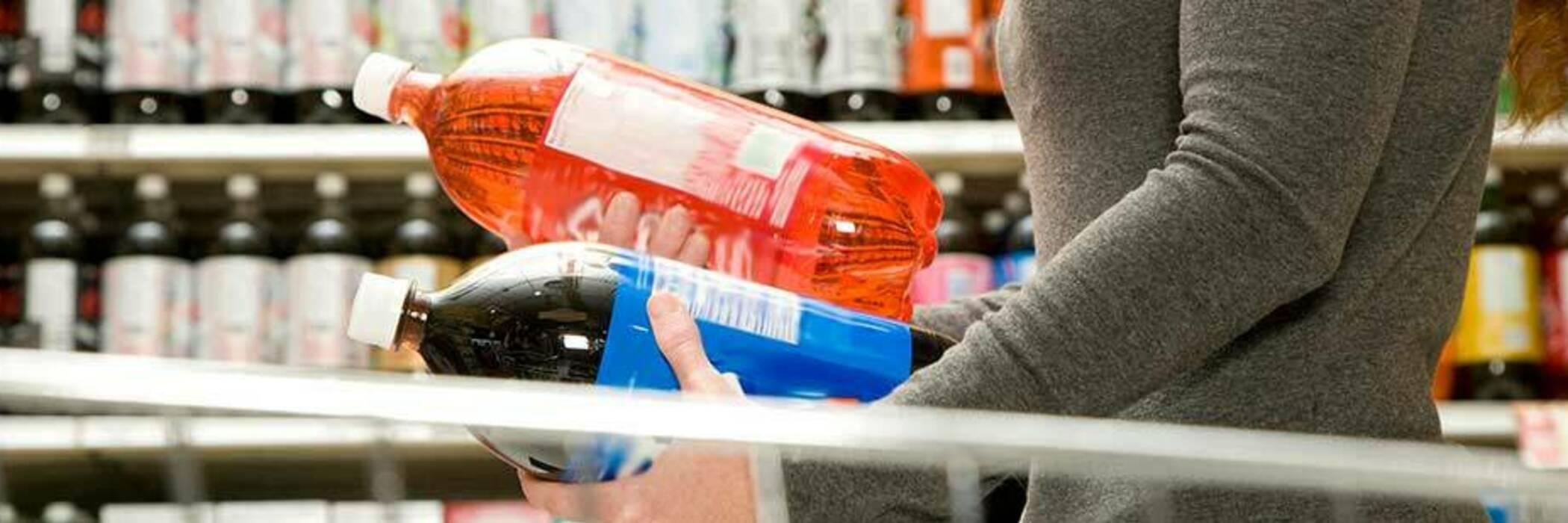 woman comparing soft drink bottles in supermarket