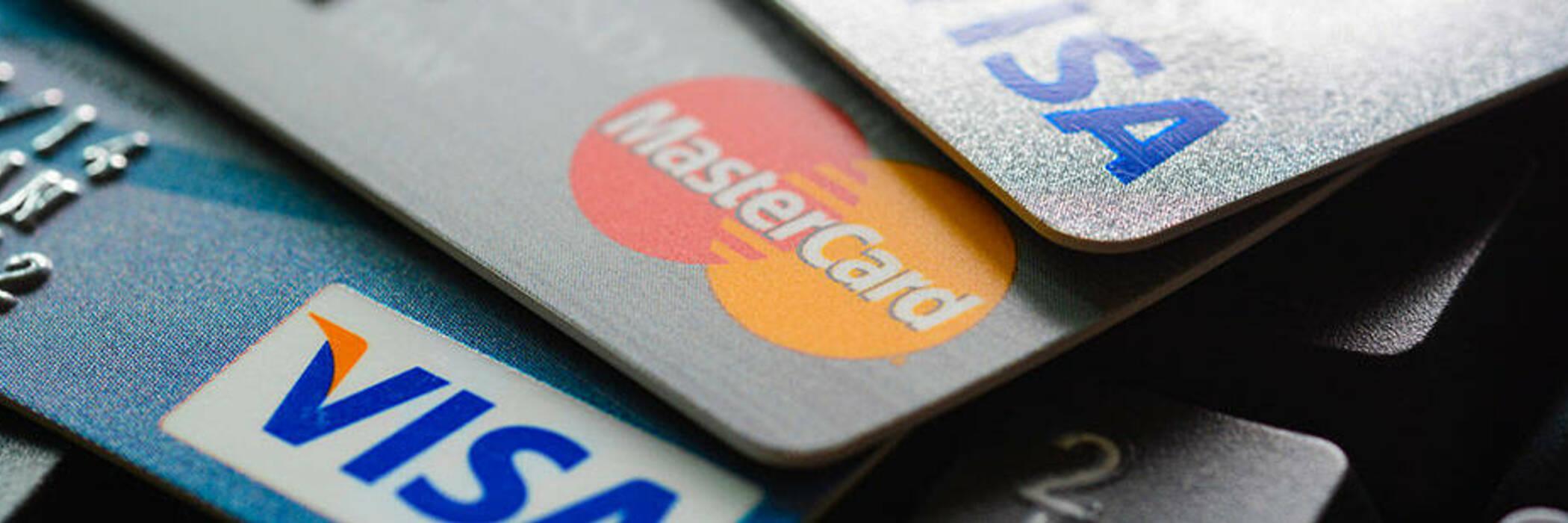 Stack of Visa and MasterCard credit cards on keyboard.