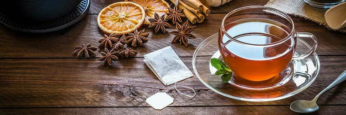 Filled tea cup surrounded by a teaspoon, teapot, teabag and ingredients.