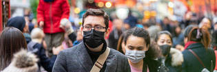 Man and woman wearing face masks in crowd of people.