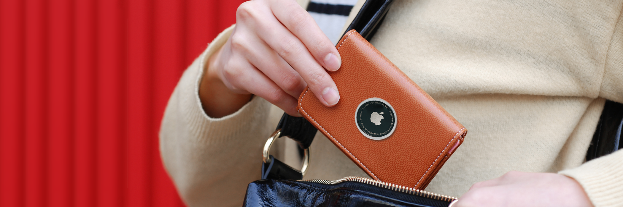 Woman pulling wallet from handbag with Apple Airtag bluetooth tracker attached.