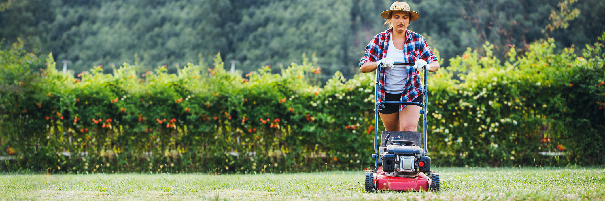 Middle aged woman mowing her lawn.