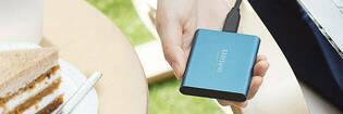 Hand holding a metallic blue Samsung hard drive
