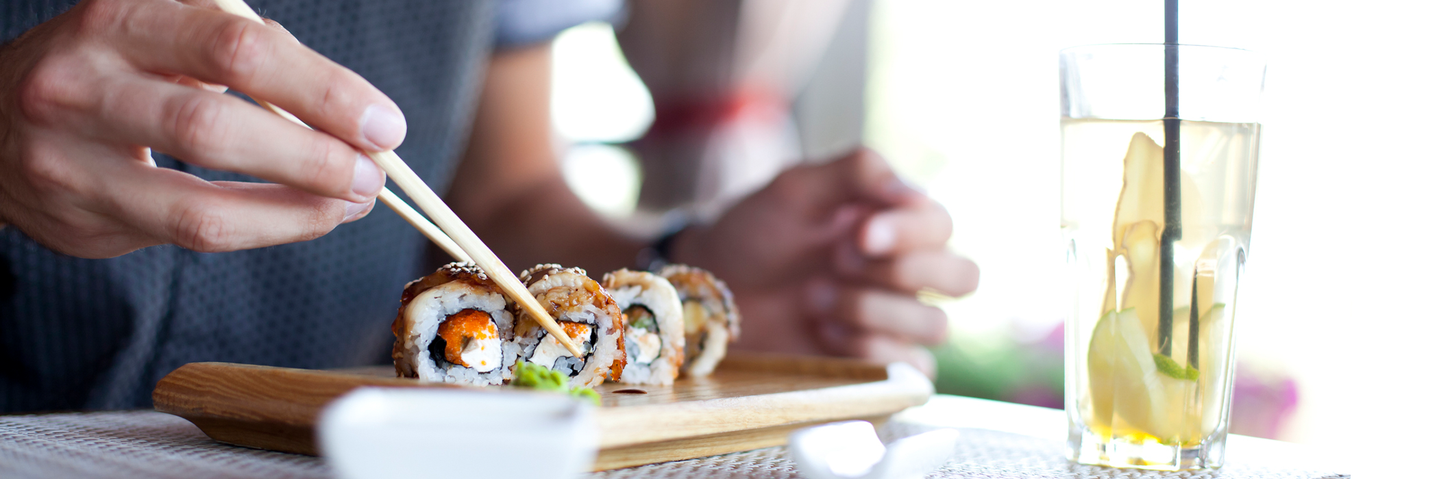Side view of a young men eating sushi.