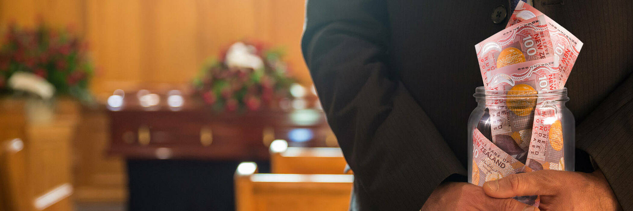 A funeral director holding a jar of cash in a church with a coffin in the background.