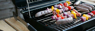 Photography of meat and veggies cooking on a barbecue.