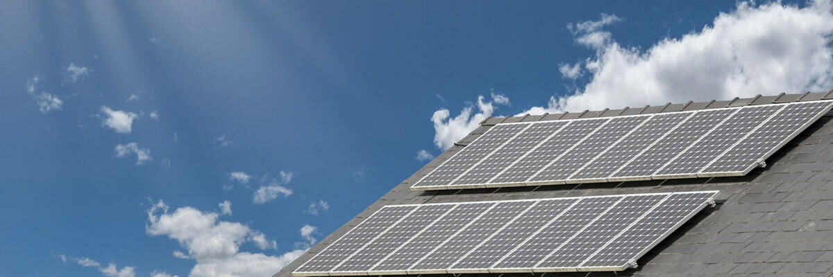Solar panels on roof of house against blue sky.