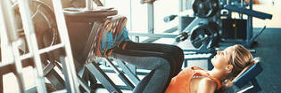 Woman using leg press machine at gym