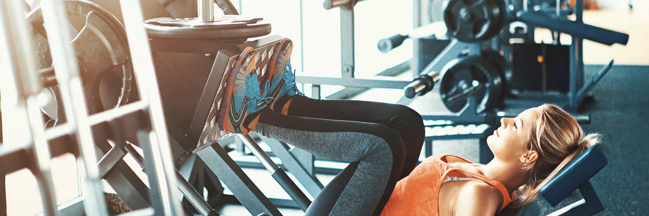Woman using leg press machine at gym