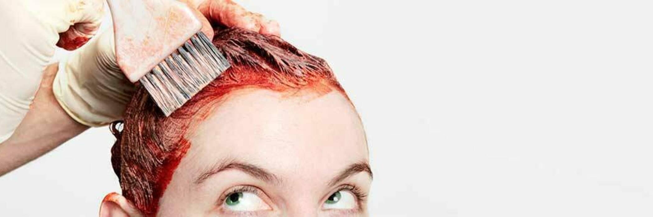Brushing red dye onto hair.