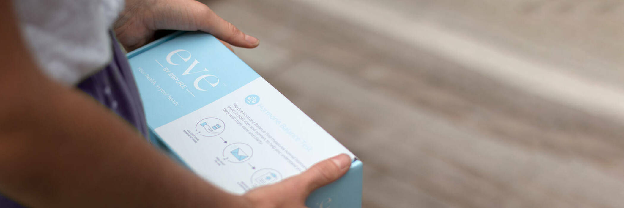 Woman holding Eve Hormone Balance Test kit