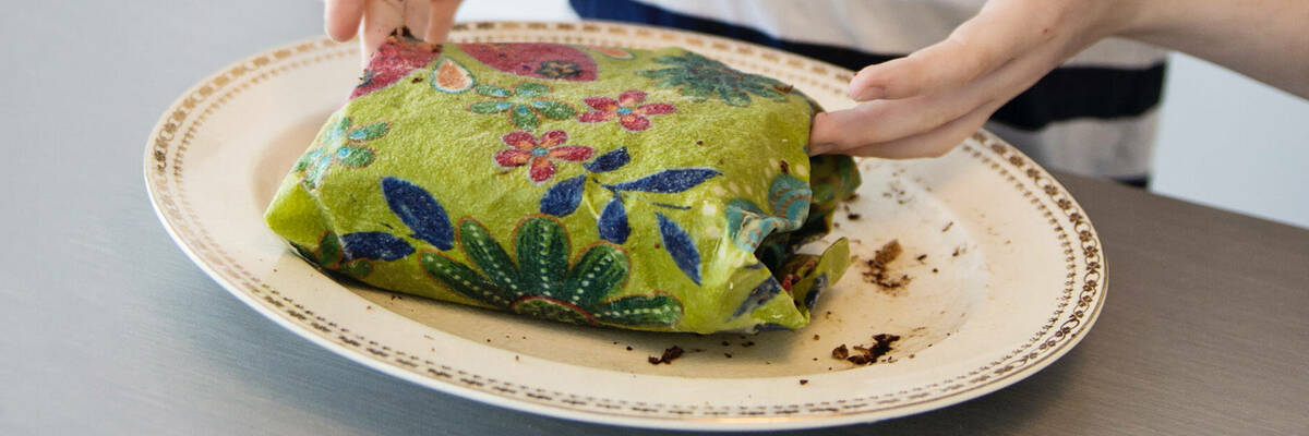 Girl wrapping food in beeswax wrap.
