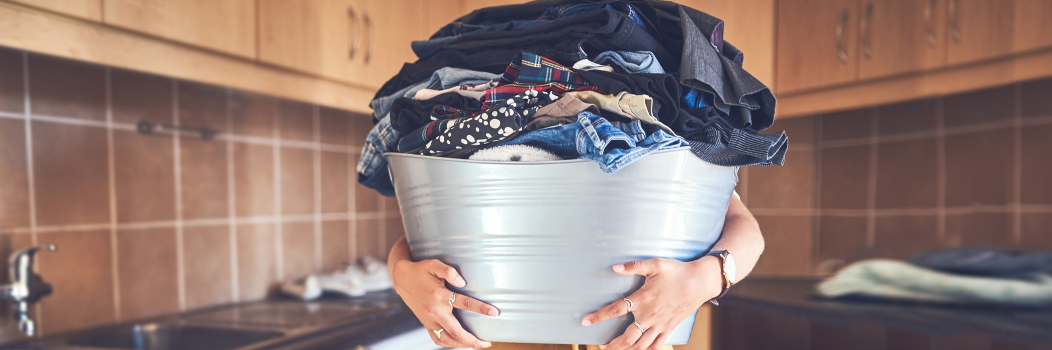 Shot of an unrecognizable woman holding overloaded laundry basket.
